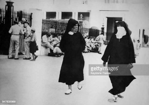 Des femmes voilées passent devant des GIs qui attendent le bus pour retourner à la base militaire francoaméricaine de SidiSlimane au Maroc