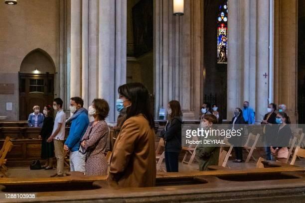 Des fidèles portant des masques de protection assistent à la première messe dominicale à la Primatiale Saint Jean lors du déconfinement après la...