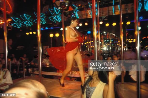 Des filles nues se produisent dans un sex show dans un bar de la capitale en juin 1994 en Thailande