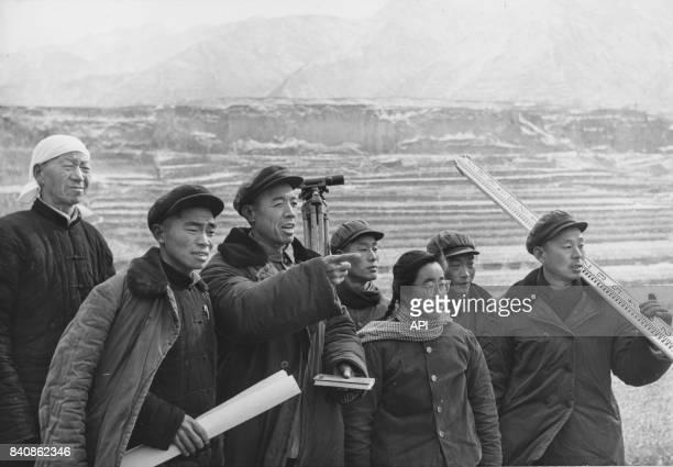 Des fonctionnaires viennent aider les paysans pour la construction d'une ferme dans la province de Henan le 27 mars 1975, Chine.