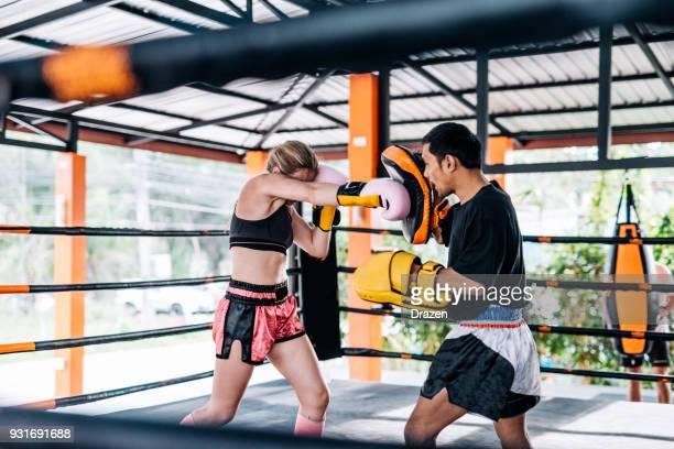 des gens de partout dans le monde exercent le muay thai dans un camp en thaïlande - muay thai imagens e fotografias de stock