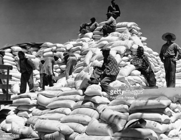 Des Grecs font une pause dans le déchargement des sacs d'aide alimentaire avant de les distribuer dans le pays circa 1940 à Athènes en Grèce