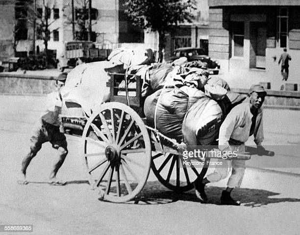 Des habitants rejoignent les ruines de leurs demeures en tirant une charrette remplie de baluchons à Tokyo Japon le 26 septembre 1945