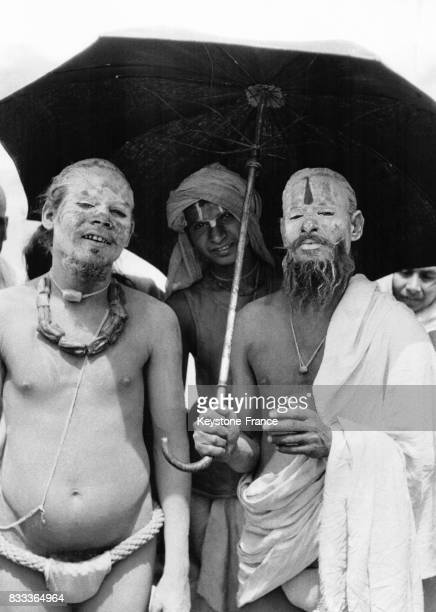 Des Hindous le visage peint photographiés sous un parapluie lors des festivités à Haridwar Inde en 1957