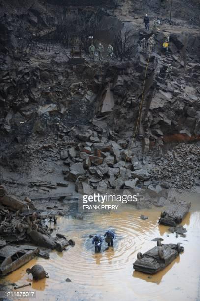"""Des hommes d'une unité de gendarmerie spécialisée dans les risques chimiques explorent le fond d'un étang pollué du site du """"Trou bleu"""" à..."""