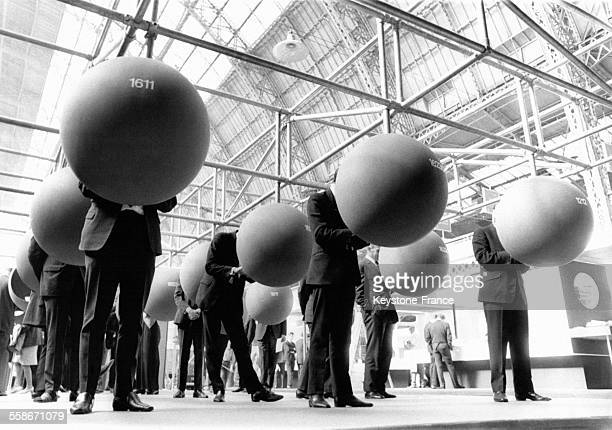 Des hommes sont penchés sur des calculateurs électroniques suspendus dans des sphères lors d'un événément d'affaires le 29 septembre 1969 à Londres,...