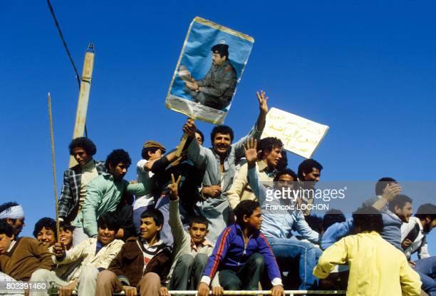 Des Irakiens brandissent le portrait de Saddam Hussein dans les rues pendant le conflit entre l'Iran et l'Irak le 25 février 1984 en Irak