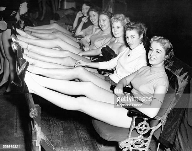 Des jeunes femmes assises sur des strapontins à l'Adelphi Theatre montrent leurs jambes lors de l'audition des jambes parfaites par un photographe en...