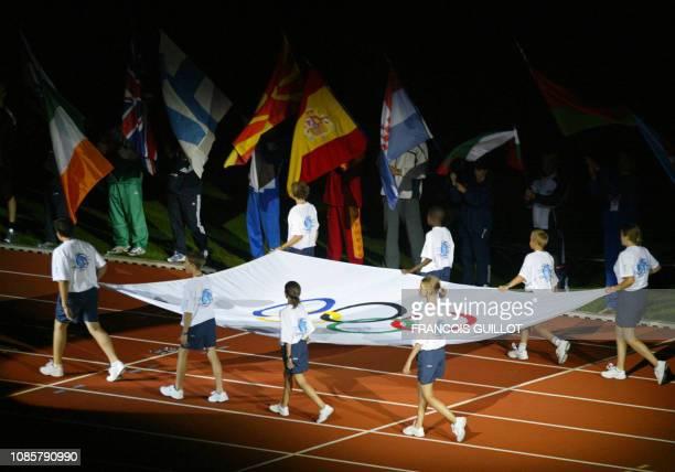des jeunes gens défilent avec le drapeau olympique le 27 juillet 2003 au stade Charléty à Paris lors de la cérémonie d'ouverture du 7e festival...