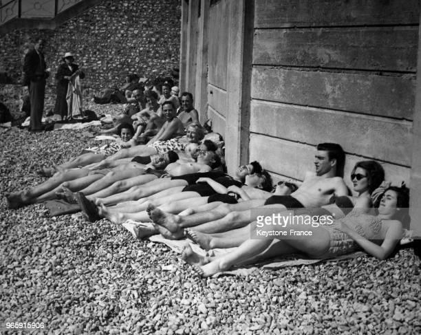 Des jeunes gens en maillots de bain bronzent allongés sur des serviettes sur la plage le jour de Pâques le 14 avril 1952 à Brighton RoyaumeUni