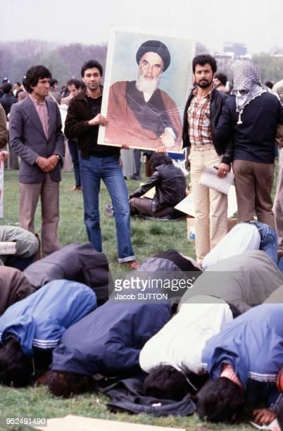 Des manifestants affichent leur soutien à l'Ayatollah iranien Khomeiny lors de la guerre entre l'Iran et l'Irak et font leur prière vers La Mecque en...