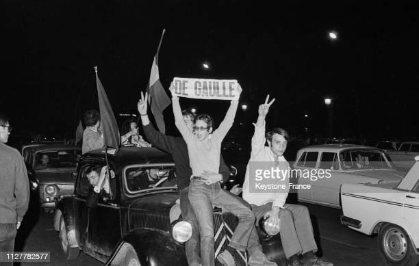 Des manifestants assis sur une voiture brandissent des drapeaux tricolores et un fanion au nom du général de Gaulle à Paris France le 31 mai 1968