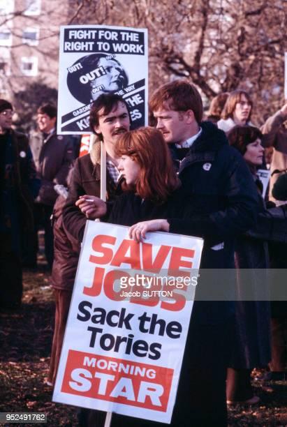 Des manifestants défilent pour protester contre la politique dure du Premier ministre britannique Margaret Thatcher caricaturée sur les pancartes du...
