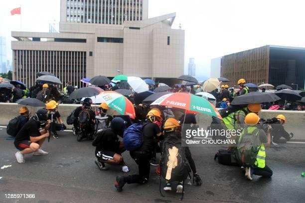 Des manifestants se protegent des tirs lacrymos de la police durant l'encerclement et l'assaut du bureau de Liaison de Beijing dans le quartier de...