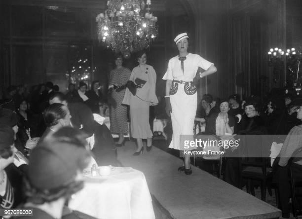 Des mannequins défilent sur le podium en présentant des modèles de haute couture à l'hôtel des Deux-Mondes le 22 janvier 1935 à Paris, France.