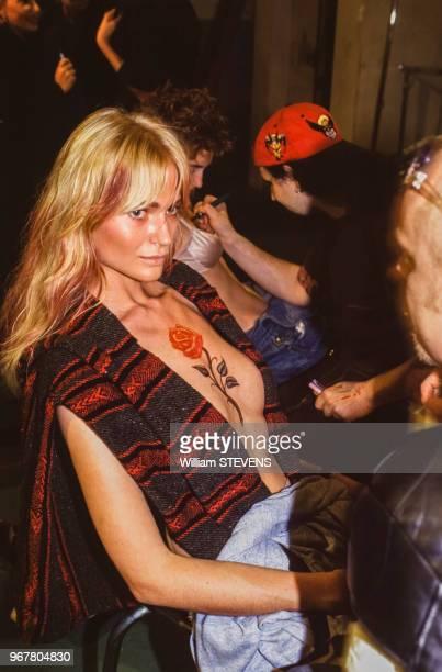 Des mannequins se font maquiller dans les coulisses lors du défilé de la collection printempsété le 17 octobre 1995 à Paris France