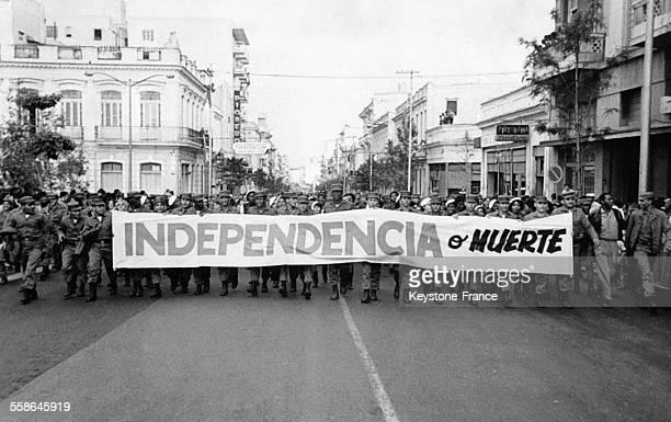 Des membres armés révolutionnaires en uniforme militaire défilent en tenant une pancarte 'L'indépendance ou la mort' dans la rue San Lazaro en...