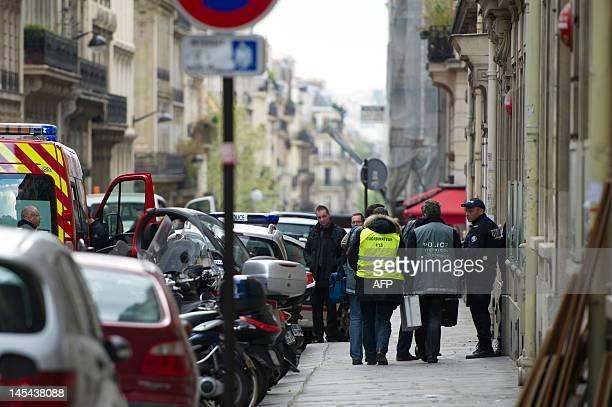 Des membres de la police scientifique arrivent le 13 avril 2012 à Paris dans un immeuble où une personne a été grièvement blessée dans un cabinet...