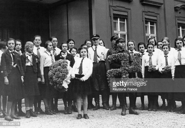 Des membres des Jeunesses Hitlériennes présentent un bouquet de fleurs et une couronne en forme de croix gammée pour offrir au président du Reich le...