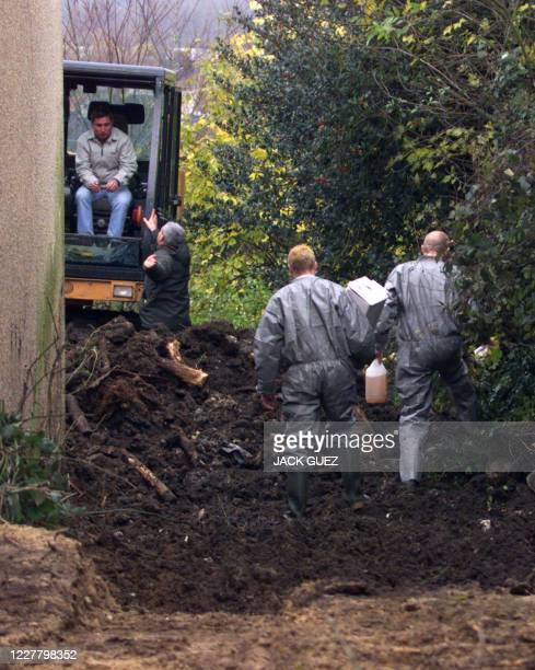 Des membres des services d'hygiène déterrent, le 26 novembre 2001 à Saint-Cyr-l'Ecole, des cadavres de chiens, retrouvés dans le jardin de la maison...