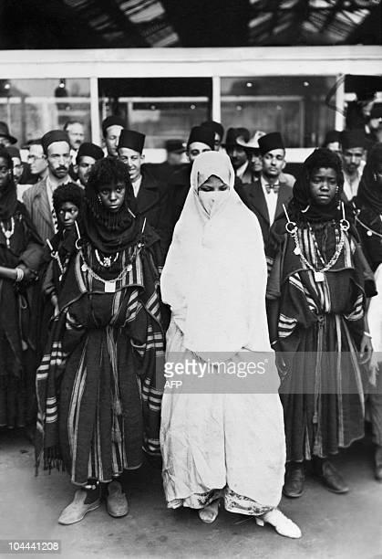 Des membres d'une délégation amenée d'Algérie alors colonie française sont photographiées revêtues de leurs costumes traditionnels alors qu'elles...