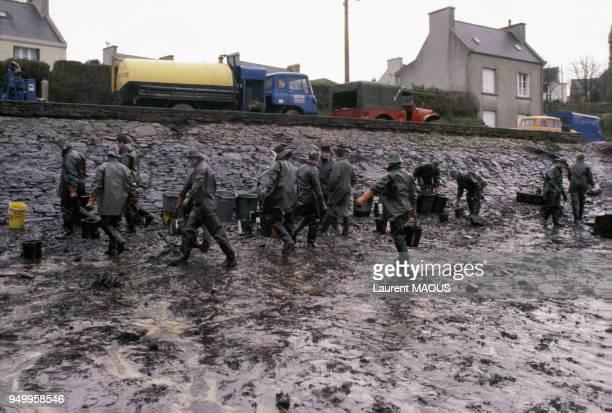 Des militaires nettoient une plage souillée par le pétrole après le naufrage du pétrolier Amoco Cadiz en mars 1978 à Portsall France