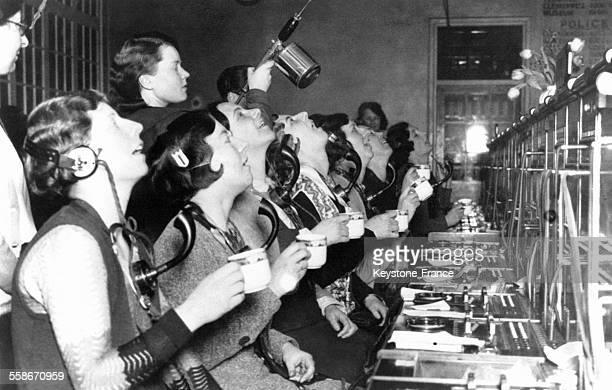 Des opératrices effectuent un bain de bouche désinfectant afin de lutter contre l'épidémie de grippe qui sévit dans une centrale téléphonique circa...