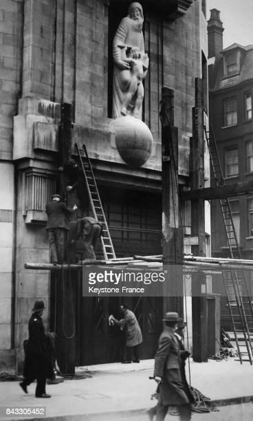 Des ouvriers démontent l'échafaudage qui entourait la statue représentant 'Prospero et Ariel' sur la façade de la BBC à Londres RoyaumeUni le 15 mars...