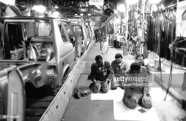 Des ouvriers musulmans font leur prière à genoux dans l'atelier près de la chaîne de montage des voitures dans une usine Talbot le 18 juillet 1983 à...
