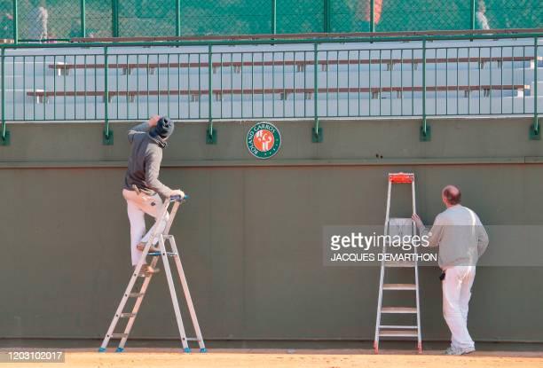 Des ouvriers remettent en état les tribunes d'un court de tennis le 09 avril 2010 au stade de Roland-Garros à Paris. Le tournoi de tennis de Roland...