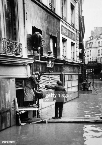 Des Parisiens évacuent leurs habitations en marchant sur des planches flottant sur l'eau lors de la crue de la Seine en 1910 à Paris France
