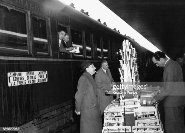 Des passagers du SimplonOrientExpress en provenance d'Athènes achètent des journaux sur le quai à leur arrivée en mars 1951 à Venise Italie