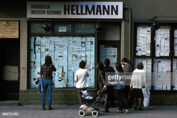 Des passants regardent la vitrine d'une agence immobilière àa BerlinEst Allemagne le 7 mai 1985