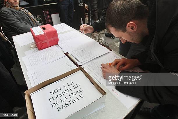Des passants signent le 13 mars 2009 à Paris devant le magasin FNAC Musique situé place de la Bastille à Paris une pétition pour soutenir les 60...