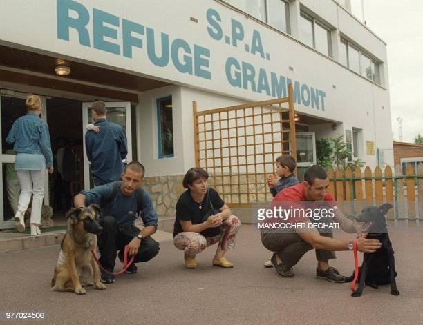 Des personnes caressent des chiens qu'ils viennent d'adopter le 17 août 1999 au refuge pour chiens et chats abandonnés de Gennevilliers Pour la...