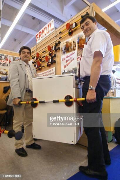 des personnes montrent l'invention de l'un des quelque 300 candidats au concours Lépine 2002 Erkul le 03 mai 2002 Porte de Versailles à Paris lors de...