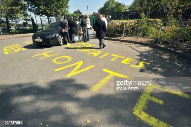 """Des personnes se tiennent sur un parking près d'une inscription à la peinture jaune """"Vous nous faites honte"""" taguée sur le sol, devant l'entrée du..."""