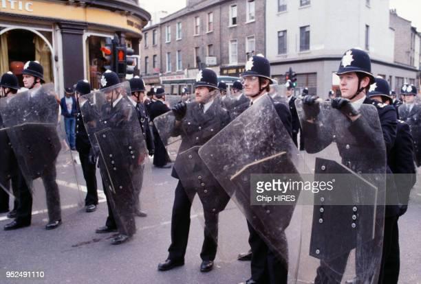 Des policiers britanniques en uniformes et abrités derrière des boucliers dans la rue lors des émeutes raciales de Brixton en avril 1981 à Londres...
