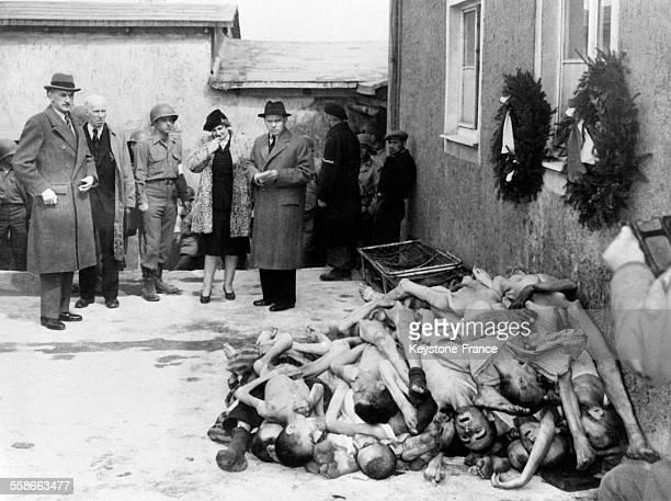 Des politiques dont madame Mavis Tate et des soldats devant un amoncellement de corps et des couronnes mortuaires au camp de concentration de...