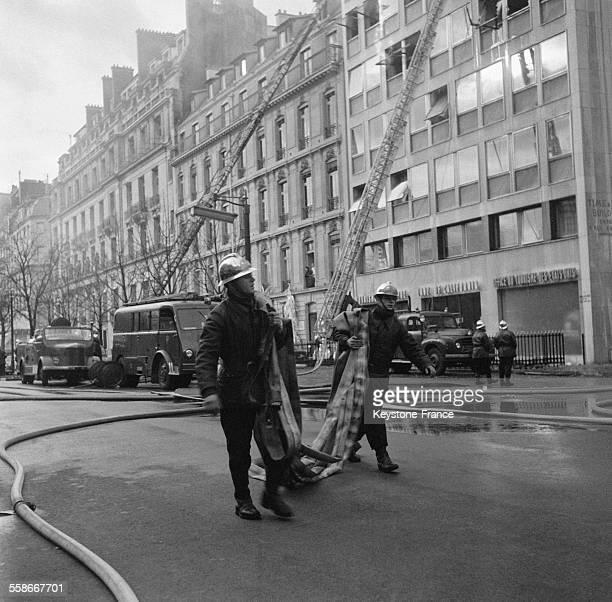 Des pompiers luttant contre l'incendie qui ravage l'immeuble à Paris France le 7 décembre 1967