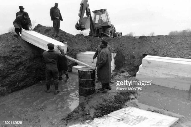 Des prisonniers volontaires procédent aux enterrements des cercueils dans des fosses communes de défunts indigents et de corps non réclamés sur l'ile...