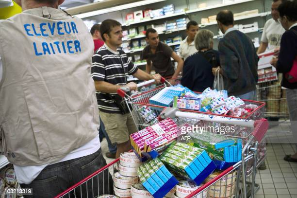 Des producteurs de lait vident les rayons de produits laitiers des rayons d'un supermarché le 03 août 2010 à Dijon lors d'une action menée par les...