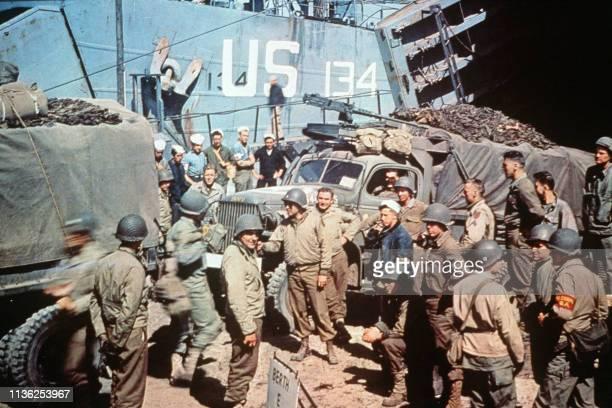 Des soldats américains qui participent au débarquement le 06 juin 1944 déchargent des véhicules militaires sortant d'une barge sur une plage de...