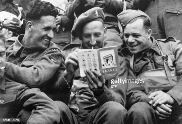 Des soldats britanniques lisent un guide touristique sur la France dans une barge de débarquement en juin 1944 durant la seconde guerre mondiale...