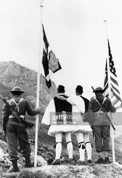 Des soldats grecs en tenue moderne ainsi que deux soldats en tenue traditionnelle plantent les drapeaux grec et américain sur le site de la Bataille...