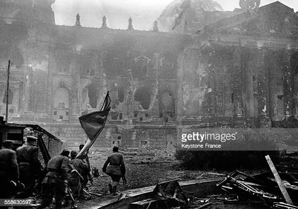 Des soldats russes agitant le drapeau de la victoire se précipitent sur le bâtiment du Reichstag à Berlin, Allemagne en 1945.