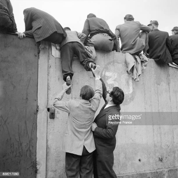 Des supporters escaladent le mur pour regarder le match de football à Paris France en avril 1951