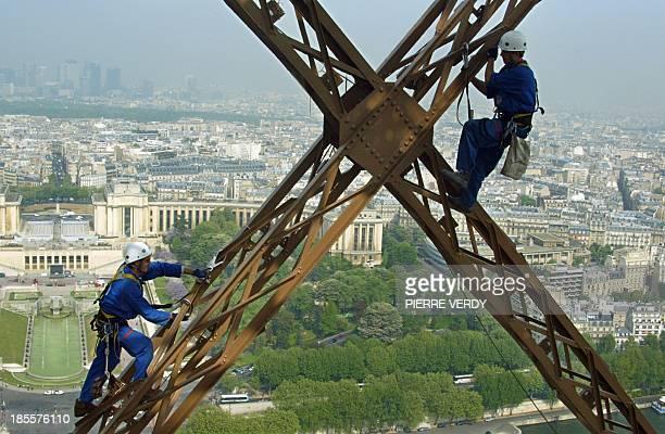des techniciens remplacent les douilles et ampoules du système électrique de scintillement de la tour Eiffel à Paris le 24 avril 2003 L'équipement...