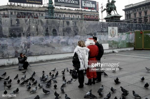 Des touristes se font photographier en compagnie du Père Noël et de pigeons sur une place en réfection à Milan Italie