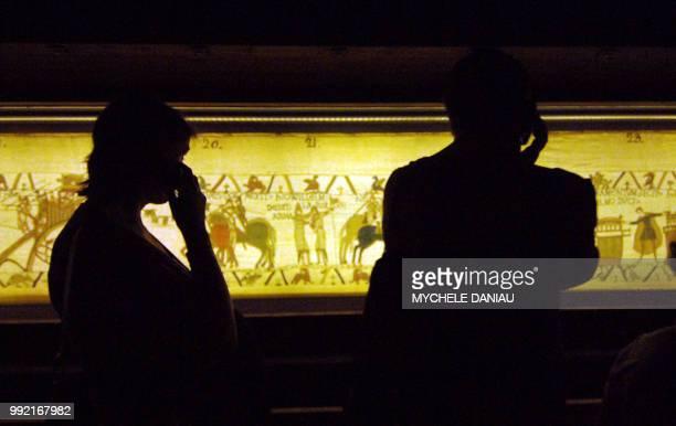 Des visiteurs observent la tapisserie de Bayeux le 27 août 2007 au musée de la tapisserie de la ville Cette broderie du 11ème siècle est inscrite...
